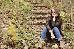 Fashion girl sitting in a park wearing sunglasses Royalty Free Stock Photo