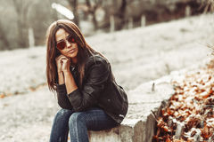 Fashion girl sitting in a park wearing sunglasses Royalty Free Stock Images