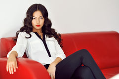 Fashion girl sitting on a red sofa at home Stock Photo