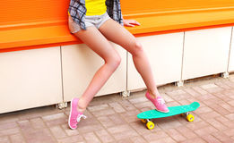 Fashion girl with skateboard over colorful orange Royalty Free Stock Photos