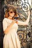 Fashion girl with smart phone outdoors Royalty Free Stock Photography