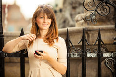 Fashion girl with smart phone outdoors Royalty Free Stock Photos