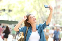 Fashion girl taking selfies in the street. Fashion girl smiling taking selfies with a smart phone in the street Royalty Free Stock Image