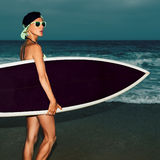 Fashion girl standing on the beach with stylish black surf board Royalty Free Stock Image