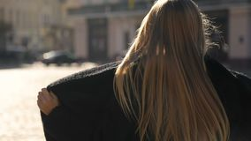 Fashion girl in street. Gorgeous fashion girl with long fair hair walking along the street, wearing black coat and gray outfit on lovely, sunny day stock video footage