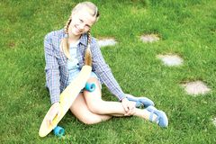 Нappy, laughing child wearing cool fashion clothing posing with colorful skateboard against green grass, urban style stock photography