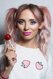 Fashion girl with two pink ponytail hairstyle Eating colourful lollipop Royalty Free Stock Photo
