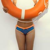 Fashion girl on the wall background with orange lifebuoy Royalty Free Stock Images