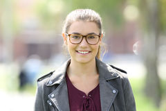Fashion girl wearing eyeglasses looking at you. Fashion girl standing wearing eyeglasses and looking at you in the street Royalty Free Stock Photography