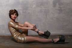 Fashion girl wearing luxurious gold dress and platform sandals Stock Photo