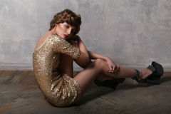Fashion girl wearing luxurious gold dress and platform sandals Royalty Free Stock Photos
