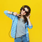 Fashion girl wearing a sunglasses and headphones. Fashion pretty cool girl wearing a sunglasses and headphones having fun over yellow background Royalty Free Stock Photography