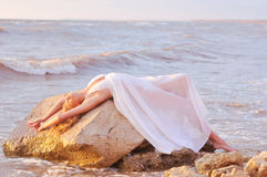 Fashion girl in a white dress. Beautiful girl lying on a rock in the sea Stock Image
