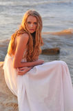 Fashion girl in a white dress. Beautiful girl sitting on a rock in the sea Stock Photos