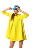 Fashion Girl In Yellow Dress And Sun Visor. Beautiful young woman in yellow mini dress and blue sun visor posing and looking away. Three quarter length studio Stock Image
