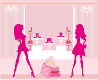 Fashion girls shopping in shoe shop Royalty Free Stock Photo