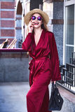 Fashion glam model beautiful pretty face sexy skinny body wear d. Ark red silk suit casual style accessory lather bag straw hat sunglasses walk on the street Stock Photo