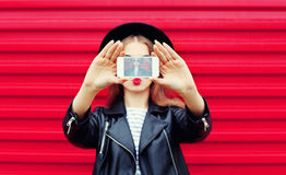 Fashion glamour woman makes self portrait on smartphone blowing lips over city pink. Background stock images
