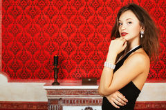 Fashion glamour woman on red vintage wall with a burning candle. Skin care, vintage rococo interior red walls and candle, model posing Royalty Free Stock Photos