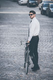 Fashion on a go. Full-length rear view of handsome well-dressed young man in sunglasses rolling his bicycle outdoors Royalty Free Stock Photos