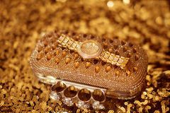 Fashion golden womens accessories. Luxury wristwatch and purse, Stock Photos