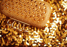 Fashion golden womens accessory. Luxurypurse on yellow sequins s Stock Photography