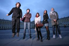 Fashion group. Group of five trendy young people jumping in a city square royalty free stock photos