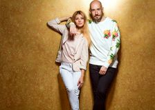 Fashion guy with a girl in the studio posing on a gold backgroun. D, the guy dressed in a sweatshot with pineapple Royalty Free Stock Image