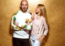 Fashion guy with a girl in the studio posing on a gold backgroun. D, the guy dressed in a sweatshot with pineapple Royalty Free Stock Photos