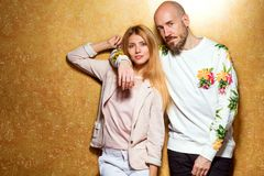 Fashion guy with a girl in the studio posing on a gold backgroun. D, the guy dressed in a sweatshot with pineapple Stock Photos