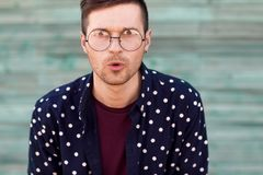 Fashion guy hipster in fashion glasses posing on a wooden blue b stock photography