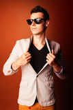 Fashion guy portrait with jacket and sunglasses on orange background studio Royalty Free Stock Image