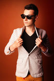 Fashion guy portrait with jacket and sunglasses on orange background studio Stock Images
