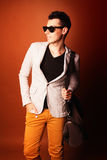 Fashion guy portrait with jacket and sunglasses on orange background studio Royalty Free Stock Images