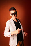 Fashion guy portrait with jacket and sunglasses on orange background studio Stock Photo