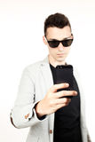 Fashion guy portrait with mobile phone on white background black glasses Royalty Free Stock Photo