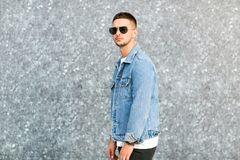 Fashion guy standing by a blue marble wall posing in sunglasses.  Stock Image