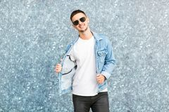 Fashion guy standing by a blue marble wall posing in sunglasses.  Royalty Free Stock Photo
