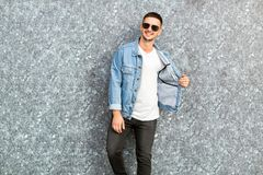 Fashion guy standing by a blue marble wall posing in sunglasses.  Royalty Free Stock Photography
