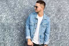 Fashion guy standing by a blue marble wall posing in sunglasses.  Stock Photo