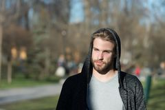 Fashion guy in stylish sportswear. Macho with beard in hood on sunny day. Bearded man wear casual sweatshirt outdoor. Lifestyle fo. R active and healthy man Stock Image