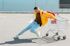 Fashion guy in sunglasses and a yellow jacket jump in a cart fro royalty free stock image