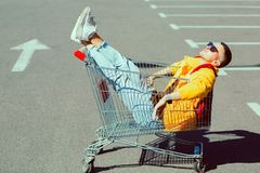 Fashion guy in sunglasses and a yellow jacket sits in a cart fro. M food in the supermarket parking stock photography