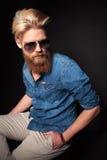 Fashion guy wearing a blue shirt sitting Stock Photos
