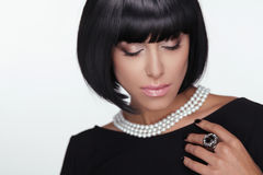 Fashion Haircut. Makeup. Sexy Lady.. Stylish Fringe. Short Hair Style. Brunette woman with jewelry pearls Stock Photography