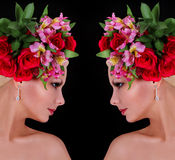 Fashion hairstyle. girl with roses. beautiful young woman with flowers in her hair over black Royalty Free Stock Photo