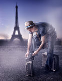 Fashion handsome man in Paris, France. Young handsome casual man Traveler in a straw hat with old brown suitcase wearing dress read guide to Paris, France Stock Photo