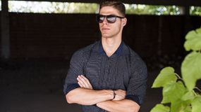 Fashion handsome young man crossing arms. Fashion handsome young man wear shirt with cuffed sleeves, dark background and green leaf,  crossing arms with serious Royalty Free Stock Images
