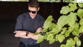 Fashion handsome young man crossing arms. Fashion handsome young man wear shirt with cuffed sleeves, dark background and green leaf,  crossing arms with serious Stock Photography