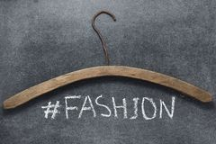 Fashion hanger. Hashtag fashion sign handwritten on blackboard with vintage wooden hanger Royalty Free Stock Images